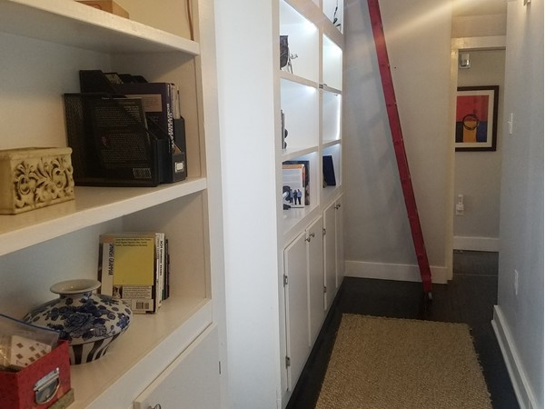 Creative hallway storage in KC homes - shelves, rope lighting, and a track ladder