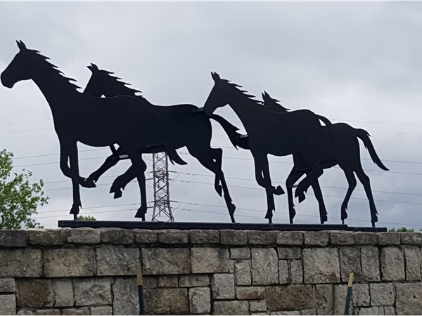 Horses galloping on the wall at the entrance to Longview Horse Farm
