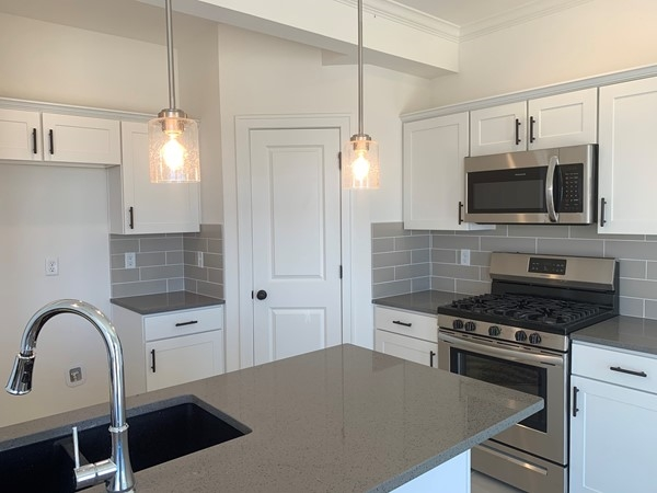 Kitchens include quartz counter tops and either white or stained cabinetry