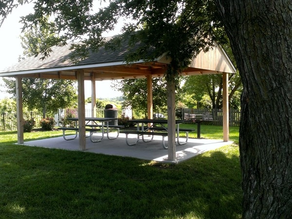 Several picnic tables and shelters next to pool and playground