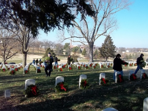 Fragrant wreaths are distributed by volunteers to gravesites of veterans