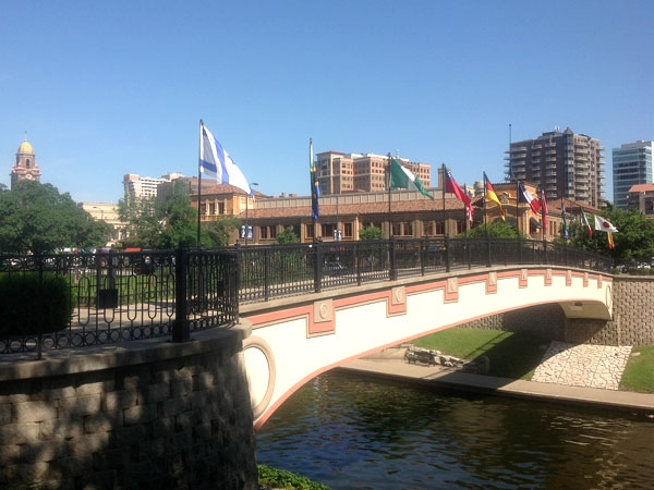 View of The Plaza across a bridge spanning Brush Creek