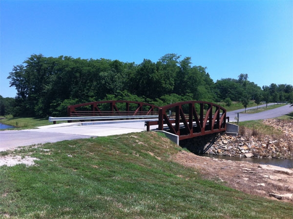 A steel bridge welcomes visitors to the Lansing City Park.