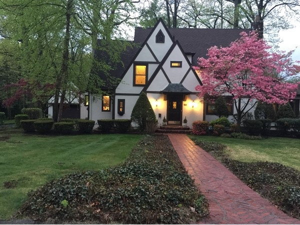 Majestic Tudor home in Goodwin terrace at dusk.  Bogert's Pond is behind the house