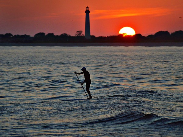 Sunset at the Cove makes a beautiful setting for this paddle surfer