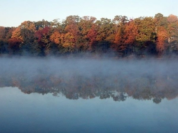 Farrington Lake with a scenic foggy water view  and turning leaves of the season in North Brunswick