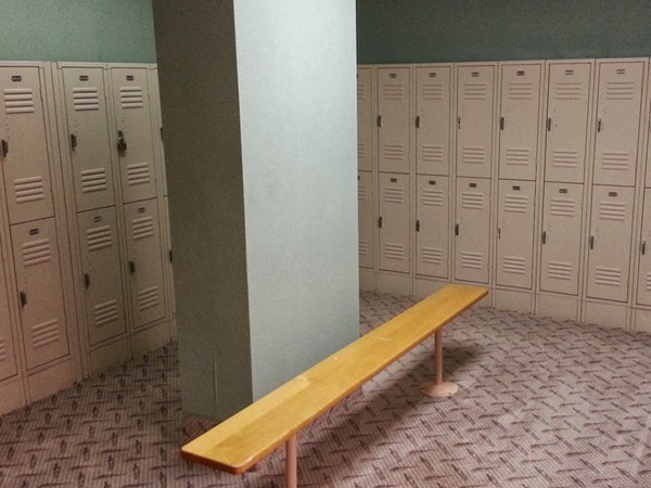 Adjacent to the fitness room is a men's locker room