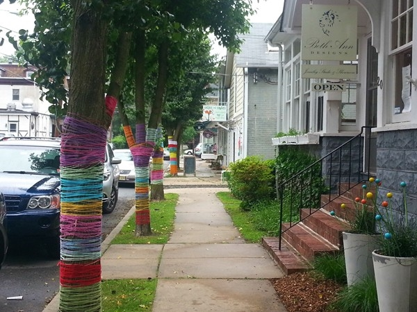 A side street in Hopewell Borough with shops and whimsical yarn-wrapped trees