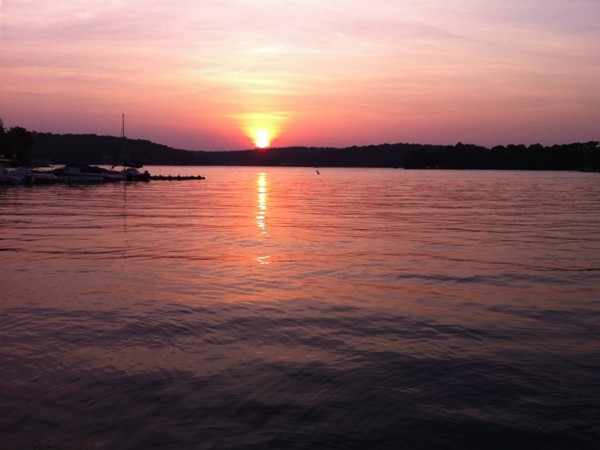 The sun sets over Lake Hopatcong as boats run across the calm waters