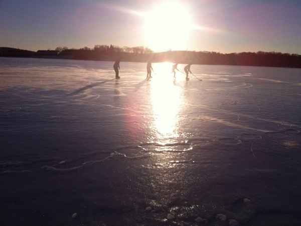 Some local boys skate around on the lake practicing skating and puck skills.