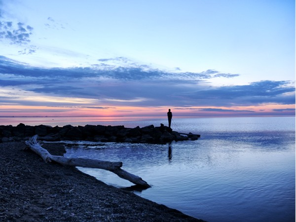 A lone fisherman at sunset in Webster Park