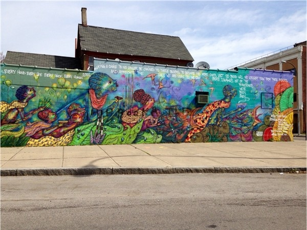 A colorful wall mural adorns the corner of Frost Avenue and Genesee Street
