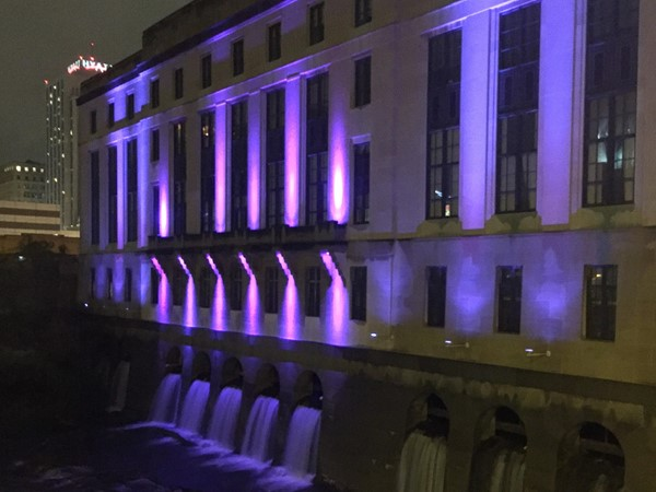 The backside of Central Public Library creates a beautiful scene at night along the Genesee River